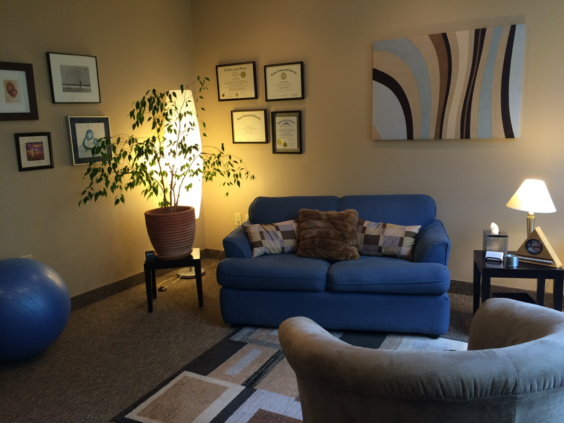 blue couch and pillows situated in a beige office with plants, photos and an abstract painting.